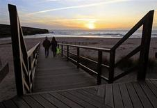 A couple walks to the beach during sunset at Lisandro beach on the Atlantic sea coast of Portugal, 40 km (25 miles) north of Lisbon March 20, 2013. REUTERS/Jose Manuel Ribeiro