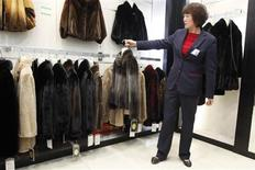 A sales woman displays a mink coat to customers at a shopping mall in Shanghai, April 4, 2013. Fueled by demand for high-end clothing and luxury home goods among China's burgeoning middle class, U.S. exports of mink pelts to China jumped to a record $215.5 million last year - more than double both the value and volume shipped in 2009. REUTERS/Aly Song