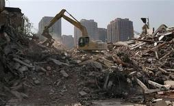 An excavator is used to demolish a building near a residential complex in Zhengzhou, Henan province April 7, 2013. REUTERS/Barry Huang