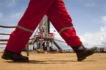 An oil worker walks past a drilling rig at an oil well operated by Venezuela's state oil company PDVSA in Morichal July 28, 2011. REUTERS/Carlos Garcia Rawlins