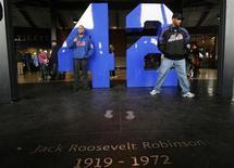 """Поклонники бейсболиста Джеки Робинсона позируют около посвященного ему постамента в Нью-Йорке, 3 апреля 2009 года. Спортивная драма """"42"""" о первом темнокожем игроке в американской бейсбольной лиге Джеки Робинсоне возглавила бокс-офис США и Канады со стартовым результатом в $27,3 миллиона. REUTERS/Lucas Jackson"""