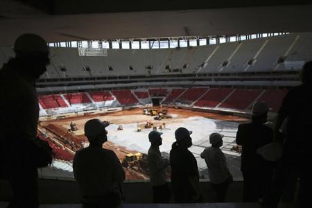 Journalists are seen inside the National Mane Garrincha Stadium undergoing construction in Brasilia April, 8, 2013. REUTERS/Ueslei Marcelino
