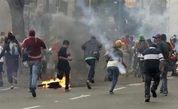 Сторонники лидера оппозиции Энрике Каприлеса разбегаются после применения полицией слезоточивого газа во время демонстрации, проходившей с требованиями пересчета результатов воскресных выборов, в Каракасе 15 апреля 2013 года. Участники политического противостояния в Венесуэле организуют во вторник массовые демонстрации в поддержку своих кандидатов на прошедших в воскресенье президентских выборах. REUTERS/Christian Veron