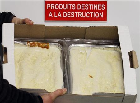 An employee displays a case of frozen beef lasagne dinners, removed from stores and prepared for destruction, under a sign on a door which reads ''Products for Destruction'' in a central purchasing warehouse in Villeneuve, Southwestern France, February 15, 2013. REUTERS/Regis Duvignau