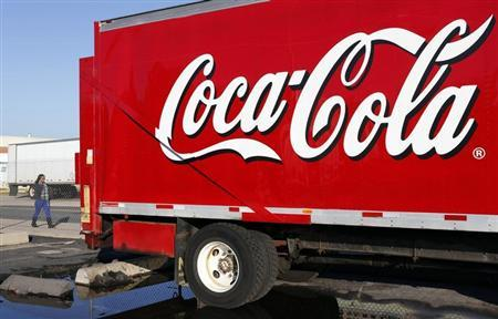 A woman walks past a Coca-Cola truck truck at a distribution center in Alexandria, Virginia October 16, 2012. REUTERS/Kevin Lamarque