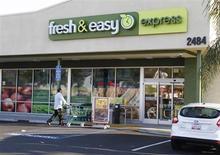 Мужчина подвозит тележку ко входу в супермаркет Fresh & Easy Express в Бербанке (Калифорния), 17 октября 2012 года. Крупнейший британский ритейлер Tesco подтвердил уход с розничного рынка США и списывает 1 миллиард фунтов стерлингов ($1,53 миллиарда) из-за своего убыточного американского отделения Fresh & Easy. REUTERS/Fred Prouser