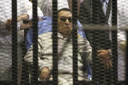 Egypt's ousted President Hosni Mubarak sits inside a dock at the police academy on the outskirts of Cairo April 15, 2013. Mubarak will stay in detention despite a judge ordering his release on bail pending a retrial over charges in complicity in the murder of protesters because he still faces other charges, court officials said on Monday. REUTERS/Stringer
