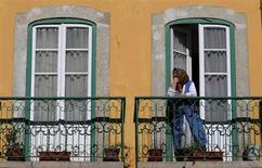 A woman watches a demonstration against government policies from her balcony in Lisbon April 17, 2013. REUTERS/Jose Manuel Ribeiro