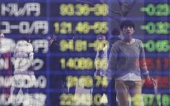 Пешеходы отражаются в информационном табло с курсами валют в Токио, 4 марта 2013 года. Иена дешевеет в ходе неровных торгов, а курс евро растет после падения накануне, вызванного слухами о новом смягчении политики Европейского центрального банка. REUTERS/Yuya Shino