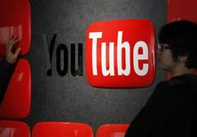 Visitors stand in front of a logo of YouTube at the YouTube Space Tokyo, operated by Google, in Tokyo February 14, 2013. REUTERS/Shohei Miyano