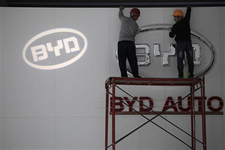 Workers work in front of the logo of Chinese car manufacturer BYD (Build Your Dreams) Auto, at the World Electric Vehicle Symposium and Exposition (EVS) in the southern Chinese city of Shenzhen in this November 4, 2010 file photo. BYD Co., one of the better known Chinese brands, may stop making conventional gasoline-fuelled cars within two years and focus on 'new energy' battery models as part of a ''re-birth plan'' to arrest a slump in sales. REUTERS/Tyrone Siu/Files