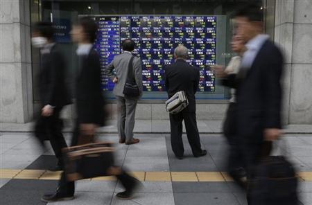 Men look at a stock index board as passersby walk past outside a brokerage in Tokyo, April 16, 2013. REUTERS/Toru Hanai