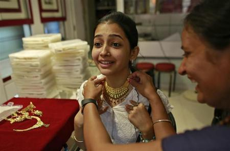 A girl tries a gold necklace inside a jewellery showroom in Mumbai, April 16, 2013. REUTERS/Danish Siddiqui