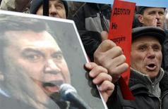 Украинцы выкрикивают лозунги и размахивают плакатами с изображением Виктора Януковича во время акции протеста в Киеве против внесения изменений в налоговое законодательство 25 марта 2011 года. Старший сын президента Украины бизнесмен Александр Янукович решил по своей воле раскрыть доходы, которые в прошлом году почти в тридцать раз превысили заработок отца, на фоне давления прессы и оппозиции. REUTERS/Gleb Garanich