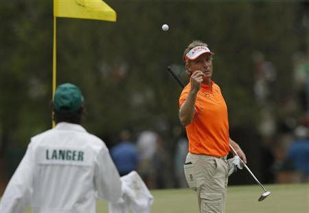 Bernhard Langer of Germany tosses his ball to his caddie before sinking a birdie putt on the third green during final round play in the 2013 Masters golf tournament at the Augusta National Golf Club in Augusta, Georgia, April 14, 2013. REUTERS/Phil Noble