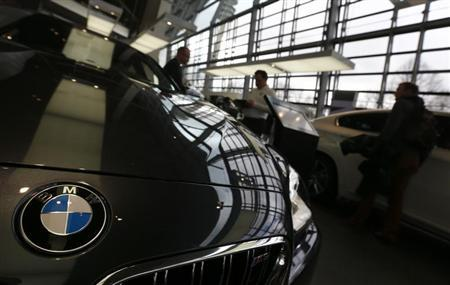 Customers walk around cars of German premium automaker BMW at the headquarters in Munich March 19, 2013. REUTERS/Michael Dalder