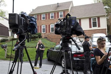 Police and members of the media stand in front of the home of Ruslan Tsarni, uncle of Tamerlan and Dzhokar Tsarnaev, the suspects in the Boston Marathon bombing, in Montgomery Village, Maryland April 19, 2013. REUTERS/Joshua Roberts