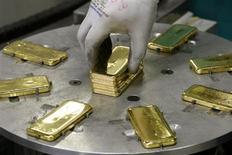 Работник завода в швейцарском городе Мендризио кладет на станок слитки золота, 13 ноября 2008 года. Цены на золото выросли более чем на 2 процента, но запасы обеспеченных золотом биржевых фондов снизились до трехлетнего минимума. REUTERS/Arnd Wiegmann