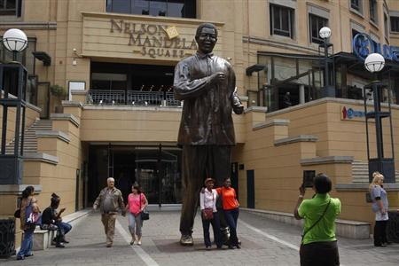 Visitors pose for photographs in front of a statue of former South African president Nelson Mandela in Sandton, Johannesburg March 30, 2013. REUTERS/Mike Hutchings