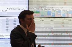 Трейдер стоит на фоне информационного табло на бирже ММВБ в Москве, 1 июня 2012 года. Российские фондовые индексы к середине торгов понедельника свели на нет утренний рост, вызванный возвращением фьючерсов на нефть Brent к отметке в $100 за баррель и частичным прояснением политической ситуации в Италии, но акции ФСК и Россетей падают в течение сессии независимо от внешнего фона. REUTERS/Sergei Karpukhin