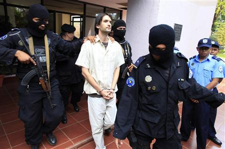 Eric Justin Toth of the U.S. is escorted after a presentation to the media at police headquarters building in Managua April 22, 2013. REUTERS/Oswaldo Rivas