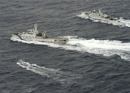 An aerial photo shows Chinese marine surveillance ship Haijian No. 66 (top) trying to approach towards a Japanese fishing boat (bottom) as Japan Coast Guard vessel Ishigaki cruises next to the Chinese ship, in the East China Sea, near known as Senkaku isles in Japan and Diaoyu islands in China, in this photo taken by Kyodo April 23, 2013. REUTERS/Kyodo