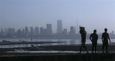 A labourer carries a sack of cement past other labourers against a backdrop of the central Mumbai financial district February 7, 2013. REUTERS/Vivek Prakash
