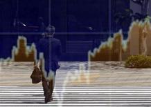Мужчина отражается в стекле перед информационным табло в Токио, 22 апреля 2013 года. Курс иены вырос, а австралийский доллар упал до шестинедельного минимума после выхода слабого показателя производственной активности в Китае. REUTERS/Toru Hanai