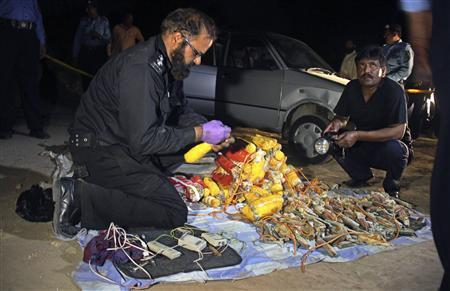 Security officials display at a police station in Islamabad, the explosive found hidden in a car (rear) that was parked near the residence of Pakistan's former president Pervez Musharraf, April 23, 2013. REUTERS/Sohail Shahzad