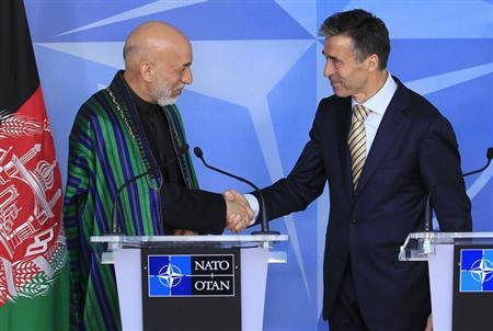 Afghanistan's President Hamid Karzai (L) shakes hands with NATO Secretary General Anders Fogh Rasmussen before a meeting at the Alliance's headquarters in Brussels April 23, 2013. REUTERS/Yves Herman