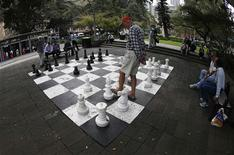 A man plays chess on a giant board at Hyde Park in central Sydney April 15, 2013. Bartenders tossing bottles in the air, a man who talks to eels and the etiquette of park chess are all part of an Australian exhibition telling the story of some of Sydney's most beloved public spaces. Picture taken April 15, 2013. To match Story AUSTRALIA-SYDNEY/ART REUTERS/Daniel Munoz