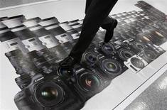 Canon a relevé ses prévisions de résultats pour l'ensemble de l'année 2013, la dépréciation du yen permettant de compenser la baisse de ses ventes d'appareils photos compacts que les consommateurs délaissent de plus en plus au profit des smartphones. /Photo prise le 24 avril 2013/REUTERS/Toru Hanai