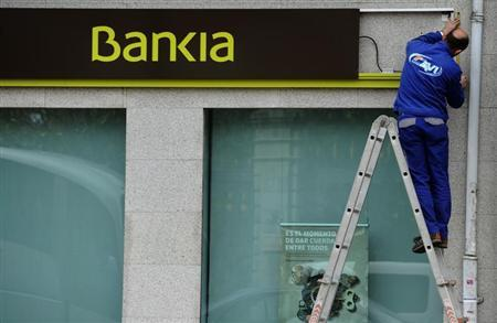 A worker changes a sign at a branch of Spain's nationalized lender Bankia in Oviedo, northern Spain April 9, 2013. REUTERS/Eloy Alonso