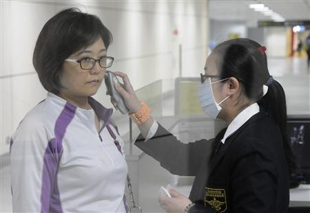 An airport staff member wearing a mask takes a passenger's temperature at Taoyuan International Airport, northern Taiwan, April 24, 2013. REUTERS/Stringer