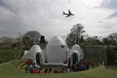 Students from Hounslow Heath infants school play around one of four adobe huts designed to help minimise the noise of aircraft landing at Heathrow airport in Hounslow, west London April 24, 2013. REUTERS/Stefan Wermuth