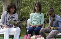 "U.S. first lady Michelle Obama (L-R) reads the children's book ""Cloudy with a Chance of Meatballs"" as her daughters Malia and Sasha look on, during the annual Easter Egg Roll on the South Lawn of the White House in Washington, April 1, 2013. REUTERS/Jonathan Ernst"