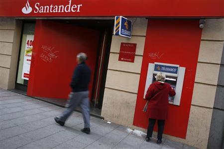 A woman uses an ATM machine at a Santander bank branch in Madrid October 16, 2012. REUTERS/Susana Vera