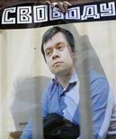 """Человек на уличной акции в Москве держит в руках плакат с портретом оппозиционного активиста Константина Лебедева 20 октября 2012 года. Лебедев приговорен к двум с половиной годам заключения за организацию массовых беспорядков перед инаугурацией Владимира Путина в прошлом году. Лебедев признал свою вину, что, по словам адвоката, помогло получить наказание """"ниже низшего предела"""". REUTERS/Sergei Karpukhin"""