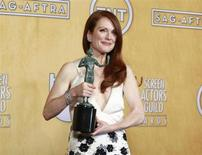 """Julianne Moore holds her award for outstanding female actor in a TV movie or miniseries for """"Game Change"""" backstage at the 19th annual Screen Actors Guild Awards in Los Angeles, California January 27, 2013. REUTERS/Adrees Latif"""