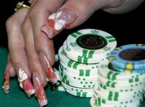 A participant picks chips at a roulette game at an event to promote legalization of casinos in Japan, in Tokyo March 6, 2007. REUTERS/Kim Kyung-Hoon