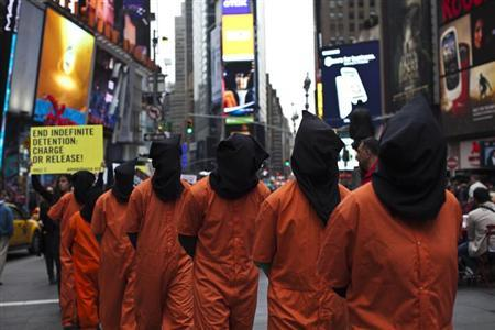 Activists dressed as prisoners demand the closure of the U.S. military's detention facility in Guantanamo Bay, Cuba while taking part in a protest in Times Square, New York April 11, 2013. REUTERS/Eduardo Munoz