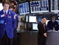 Трейдеры на Нью-Йоркской фондовой бирже отдают дань памяти жертвам взрывов в Бостоне во время минуты молчания 22 апреля 2013 года. Американские рынки акций открылись разнонаправленно в пятницу. REUTERS/Brendan McDermid