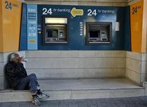 A man drinks beer near ATMs outside a branch of the Bank of Cyprus in Nicosia March 28, 2013. REUTERS/Yannis Behrakis