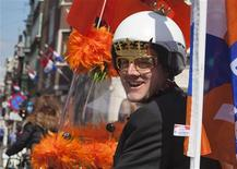 A man riding a scooter and wearing a crown on a helmet cruises the streets of Amsterdam April 28, 2013. The Netherlands is preparing for Queen's Day on April 30, which will also mark the abdication of Queen Beatrix and the investiture of her eldest son Willem-Alexander. REUTERS/Cris Toala Olivares