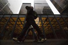 A man walks in front of buildings in the financial district in Toronto, January 28, 2013. REUTERS/Mark Blinch