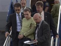 Porn movie actor Luka Rocco Magnotta, 29, accused of killing a Chinese student, Jun Lin, and sending his feet and hands in the mail to the offices of two Canadian political parties and two Vancouver schools, is escorted off a plane from Germany by Montreal police in Mirabel, June 18, 2012 in this handout photo. REUTERS/SPVM/Handout.