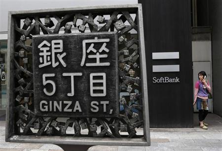 A woman holding a mobile phone stands in front of Softbank Corp's branch in Tokyo April 17, 2013. REUTERS/Yuya Shino
