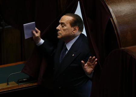 Italy's former Prime Minister Silvio Berlusconi holds his ballot as he leaves the polling booths during the third day of the presidential election in the lower house of the parliament in Rome April 20, 2013. REUTERS/Alessandro Bianchi