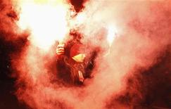 A demonstrator holds flares up as he taunts the riot police as violence breaks out at a parade celebrating Poland's national holiday in Warsaw in this November 11, 2012 file photograph. REUTERS/Peter Andrews/Files