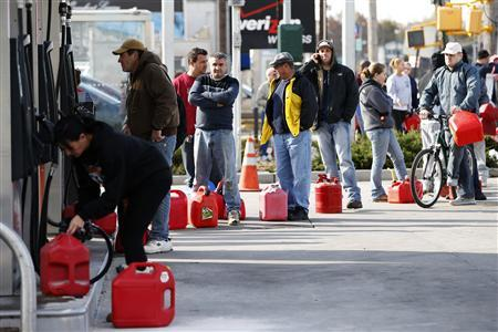 People stand in line with gas cans to fill at one of the few gas stations open on hard-hit Staten Island in New York City following Hurricane Sandy, in this November 2, 2012 file photo. REUTERS/Mike Segar/Files